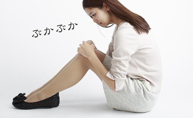 座り込んでぶかぶかの靴を見つめる女性