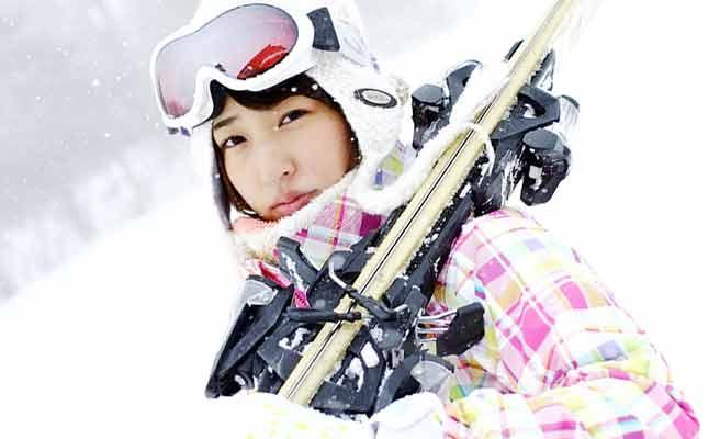 スキーを担いで歩く女性