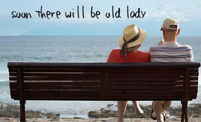 ベンチに座って海を見つめる老いた男女