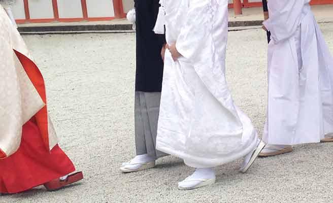 神社の巫女さんと新郎新婦が歩く