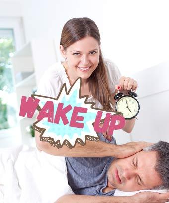 寝ている彼氏の耳元に目覚まし時計を近づける女性