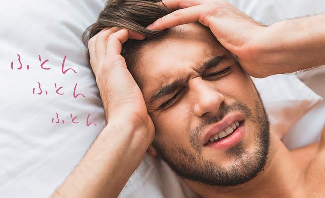 ベッドの中で目を閉じたまま頭を押さえる男性