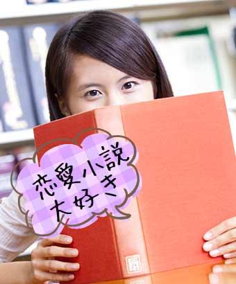 本の陰になって読書する女性