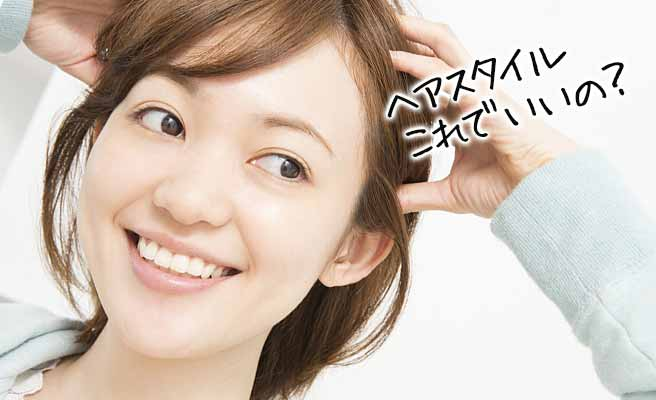 髪を両手で押さえて新しい髪型を探してる女性