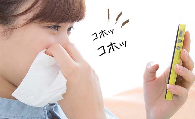 スマホに向かって軽い咳をする女性