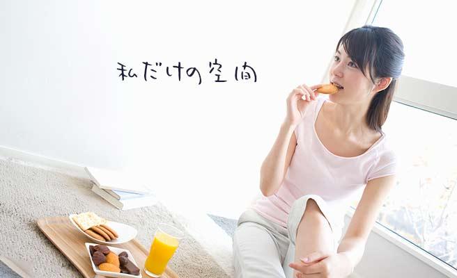 部屋の隅でゆったりおやつを食べる女性