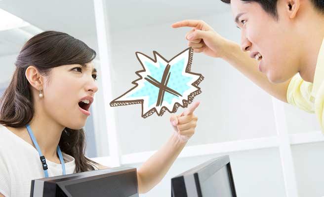 職場でデスク越しに男性と口論する女性