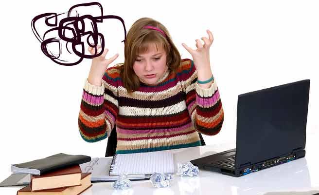 乱雑なデスクを前に混乱する女性