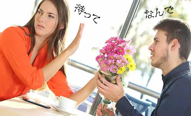 男性の差し出す花束を手で止める女性