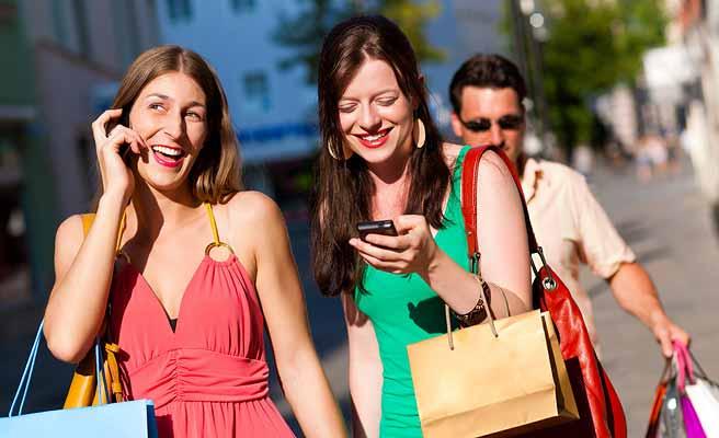スマホを見ながら並んで通りを歩く女性二人