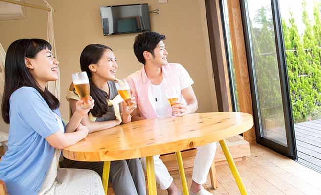 女友達と男性が一つテーブルでビールを飲んでいる