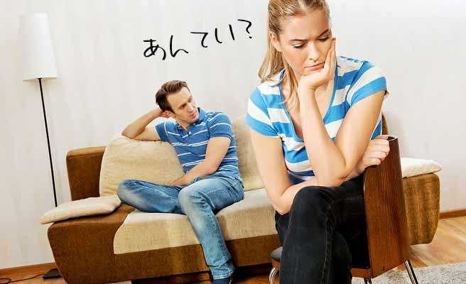 片肘ついて思案する女性と背後の無表情の男性