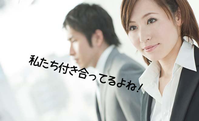 職場で男性と並んで立ち、つぶやく女性