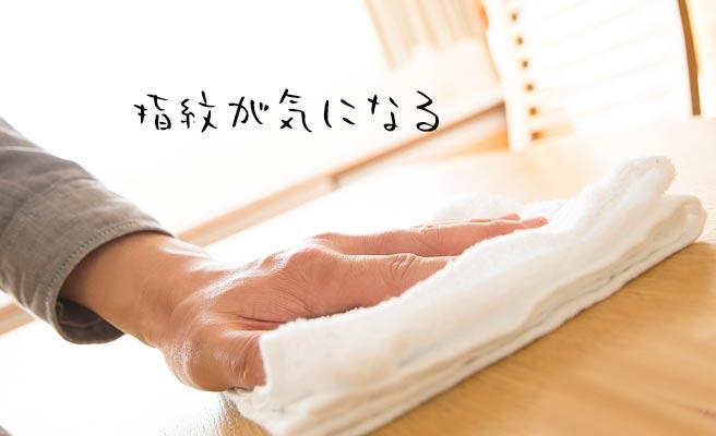 テーブルの上を布巾で拭く男性の手