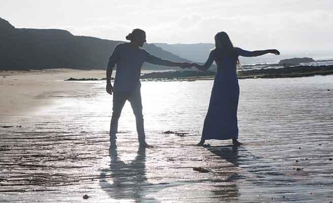 砂浜を手をつないで歩くカップル