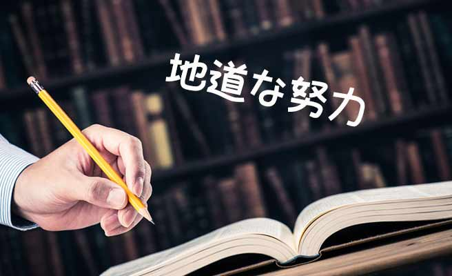 本を開いて鉛筆でチェックする男性