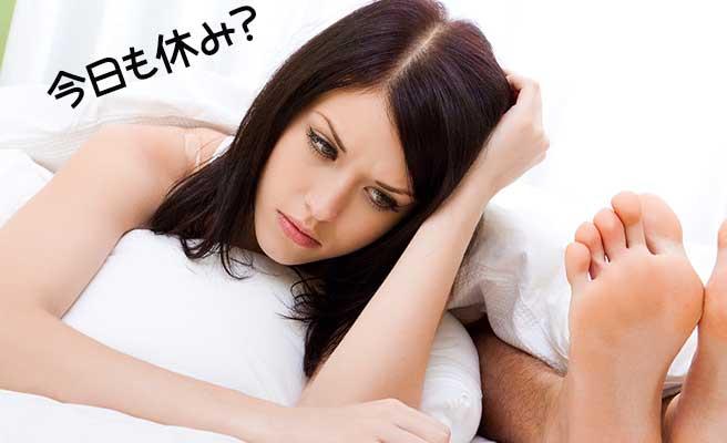ベッドに寝たままの彼氏の傍でうんざりした表情の女性