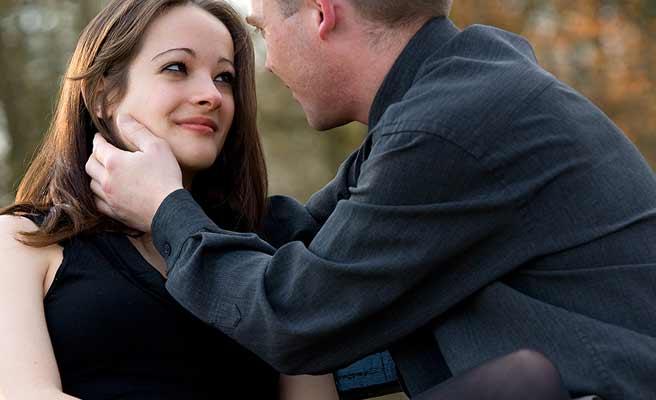 彼氏の目を見つめる女性とハグする男性