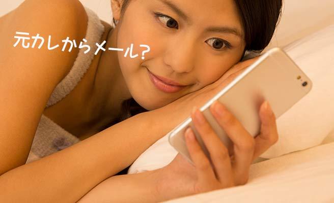 ベッドでスマホを見つめる女性