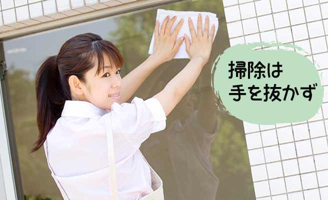 窓の外側を拭く女性