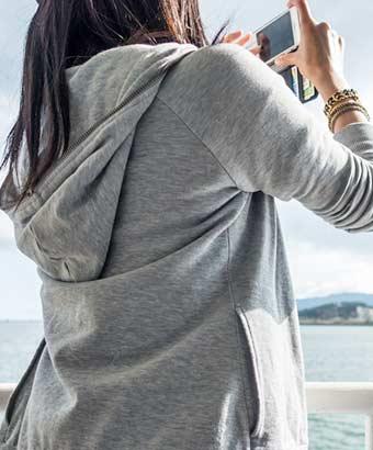 パーカーを着て戸外で写真を撮る女性