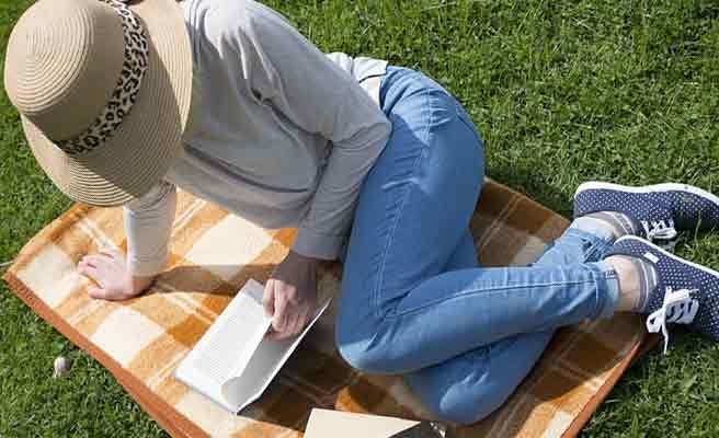 芝生の上で読書するGパンの女性