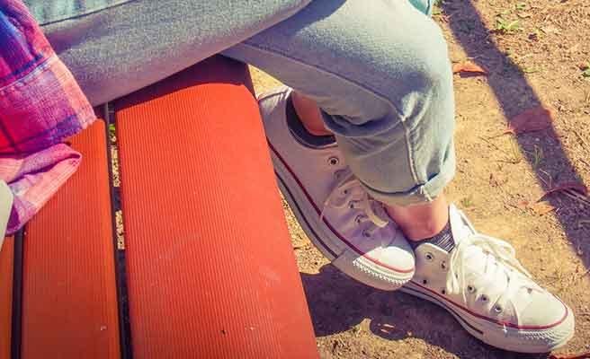 ベンチに座る女性の靴はスニーカ