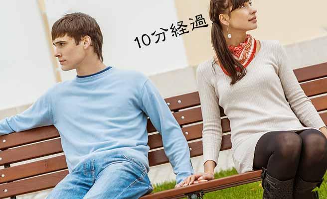 ベンチに並んで座って彼氏の手に自分の手を重ねる女性