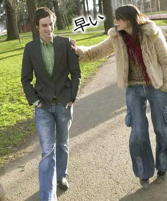 並んで歩く彼氏の腕をつかんで早いと文句を言う女性