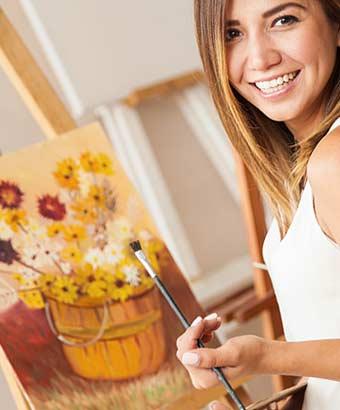 筆を手にして油絵を描く女性