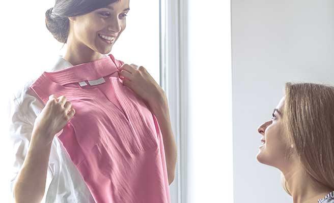ピンク色の服を自分の体に当てがい他の女性に相談する女性
