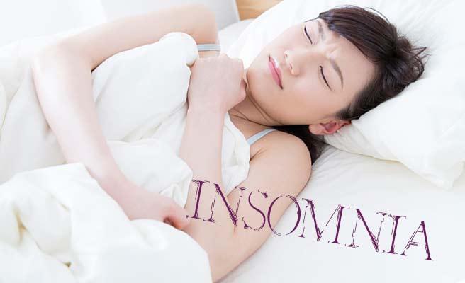 ベッドの中で寝苦しそうに眉間に皺を寄せる女性