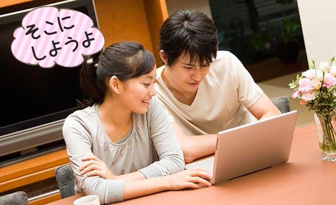 ノートパソコンを見ながら相談するカップル