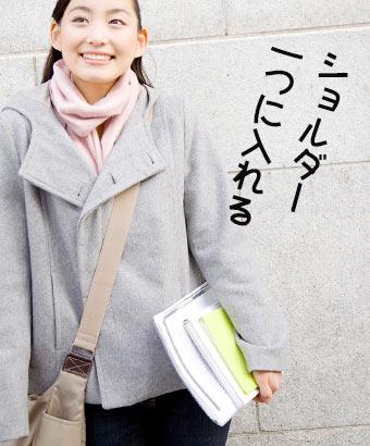 ショルダーバッグと教科書を手にもつ女子大学生