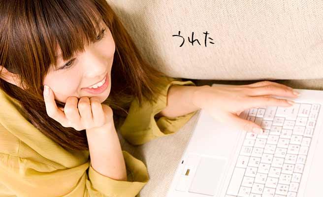 ノートパソコンを見ながら微笑む女性