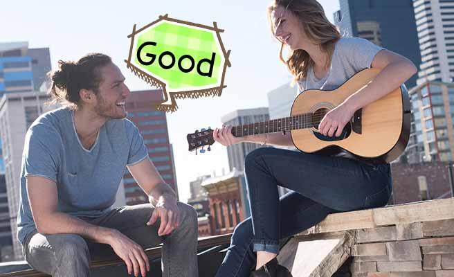 彼女の演奏するギターを聞いて笑顔の男性