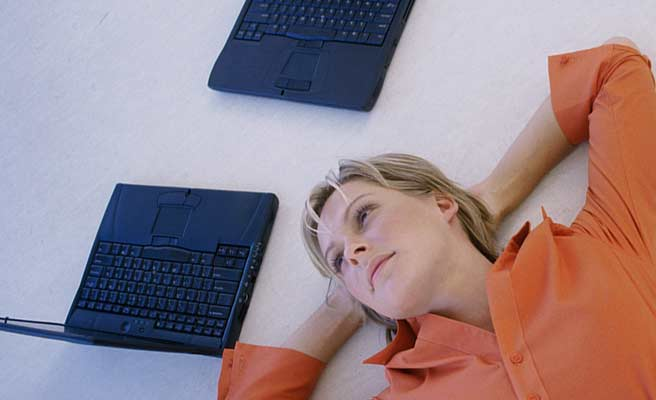 ノートパソコンのそばで腕枕で横になる女性