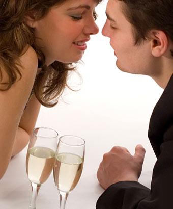 ワイングラスを間に置いて顔を寄せる男女