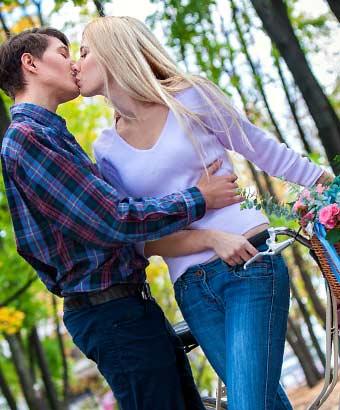 自転車を持ちながら彼氏とキスする女性