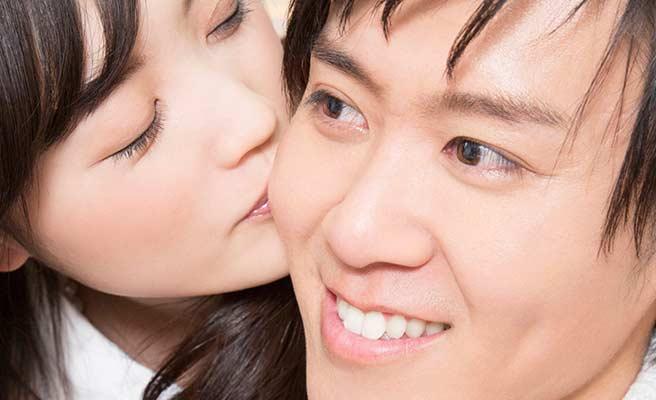 彼氏の背後からキスする女性