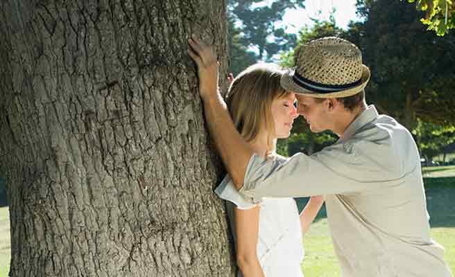 大木の陰でキスするカップル