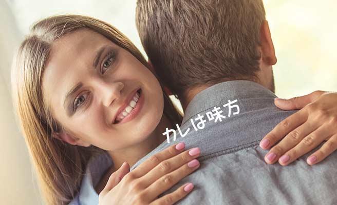 男性の肩を両手で抱いて微笑む女性