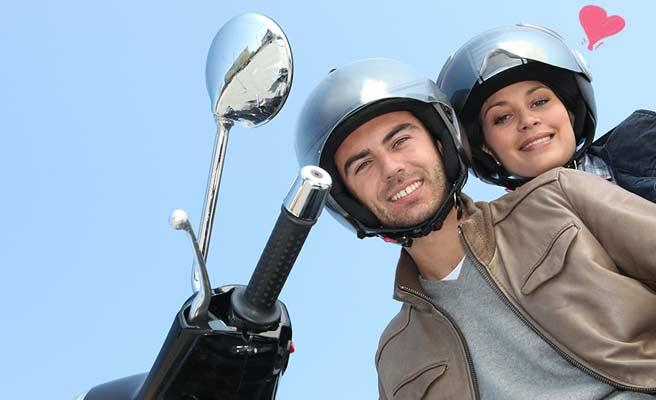 ヘルメット着用でバイクにまたがるカップル