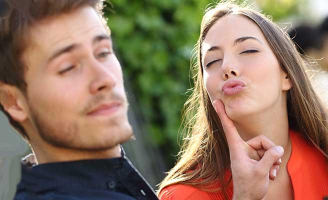唇を突き出す女性と指で制止する男性