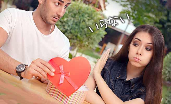 男性のプレゼントを手で拒む女性