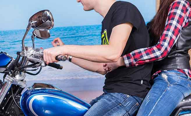バイクを運転する彼氏の体に腕を回して座る女性