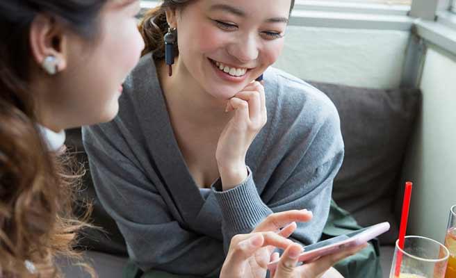 女友達とスマホを見ながら談笑する女性