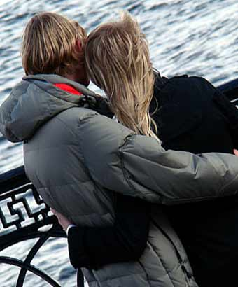 彼女を抱き寄せて水面を見つめる男性
