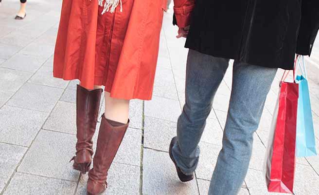 買い物袋を下げて歩く男性と手を繋ぐ女性