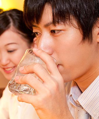 グラスを傾けながら女性の話を聞く男性